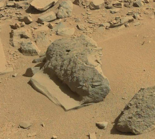 This boulder looks at first like a large rock sitting on a thin flat slab but on closer inspection appears to actually be all one formation. So how did it form? Credit: NASA / JPL-Caltech