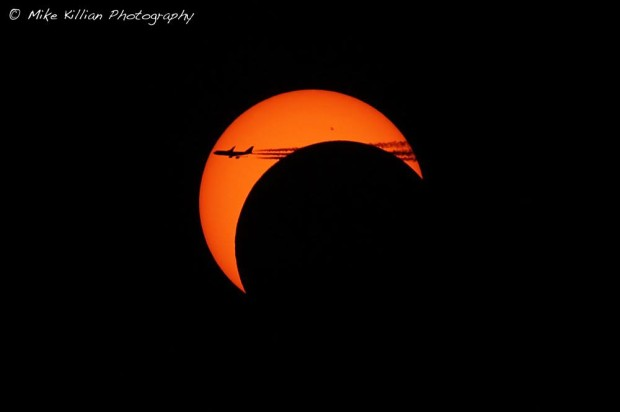 An airliner passing through the crescent eclipsed sun. Photo Credit: Mike Killian