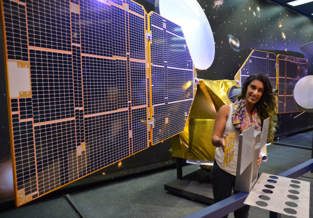 A full-scale mockup of MarCO, held by Farah Alibay, a systems engineer for the technology demonstration. A one-half-scale model of the Mars Reconnaissance Orbiter is behind her. Photo Credit: NASA/JPL-Caltech