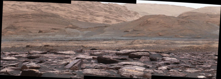 View of the path ahead for the Curiosity rover, looking toward the foothills of Mount Sharp. The various sedimentary layers on the mountain are a geological record of different environmental conditions in the past. Photo Credit: NASA/JPL-Caltech/MSSS