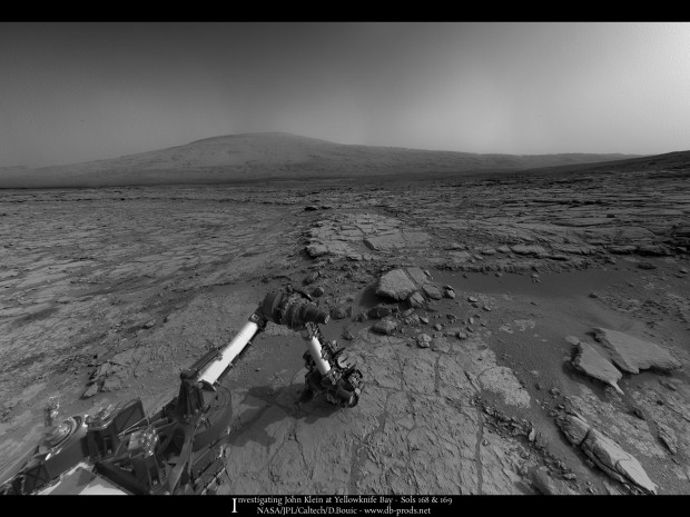 Panorama from sol 169 showing John Klein in the foreground, the rest of Yellowknife Bay in the distance and Mount Sharp on the horizon. Click for larger version. Credit: NASA / JPL-Caltech / Damien Bouic
