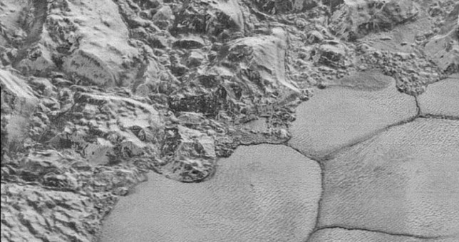 "Mountains of solid water ice which border the smooth nitrogen ice plains, giving the appearance of a ""shoreline."" On Pluto, water ice is as hard as rock. Photo Credit: NASA/JHUAPL/SwRI"