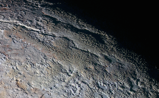 """Extended colour image showing the """"snakeskin"""" terrain in the Tartarus Dorsa region, a mixture of blue-grey ridges and other reddish material. Image Credit: NASA/JHUAPL/SWRI"""