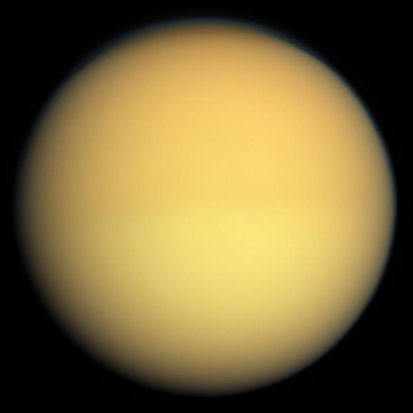 As seen by regular cameras or the human eye, Titan appears almost featureless due to the thick haze which envelopes the moon's atmosphere and obscures the surface. Photo Credit: NASA/JPL-Caltech